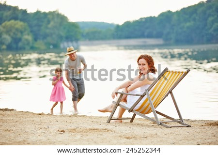 Family with daughter taking summer vacation at beach of a lake - stock photo