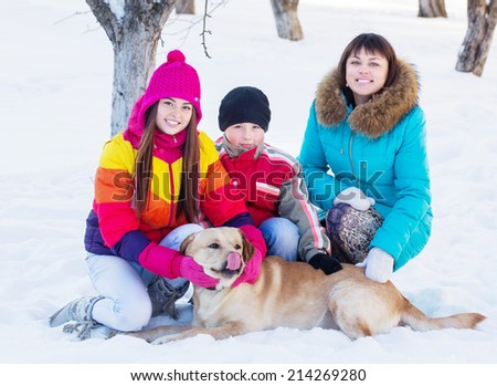 family with dog in a snowy garden - stock photo