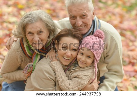 Family with Grandparents and little girl in autumn park