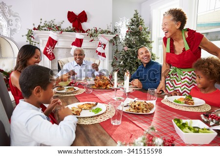Family With Grandparents Enjoying Christmas Meal At Table - stock photo
