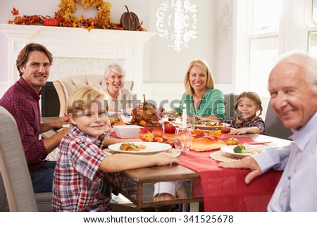 Family With Grandparents Enjoying Thanksgiving Meal At Table - stock photo