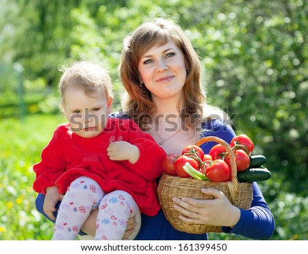 family with  harvested vegetables in garden - stock photo