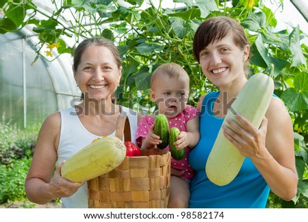 family with  harvested vegetables in greenhouse