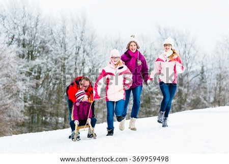 Family with kids having winter walk in snow - stock photo