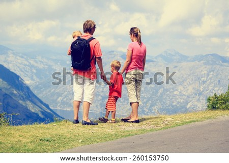 family with kids hiking in summer mountains