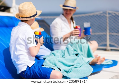Family with kids relaxing having great time sailing at luxury yacht or catamaran boat - stock photo