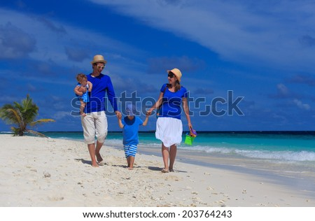 family with kids walking on tropical sand beach
