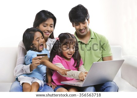 Family with laptop and credit card - stock photo