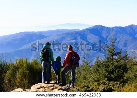 family with little child hiking in mountains