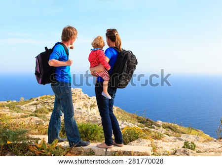 family with little daughter hiking in summer mountains - stock photo