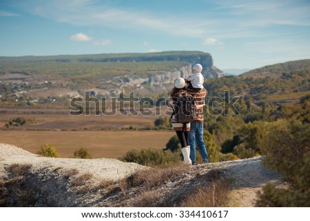 Family with little daughter resting in autumn mountains