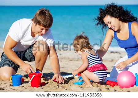 Family with little girl playing on the beach