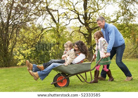 Family With Man Giving Mother And Children Ride In Wheelbarrow - stock photo