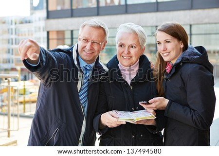 Family with map on sightseeing tour on a city trip - stock photo