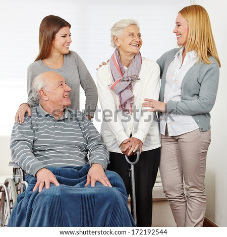 Family with mother and daughter and two senior citizens at home - stock photo