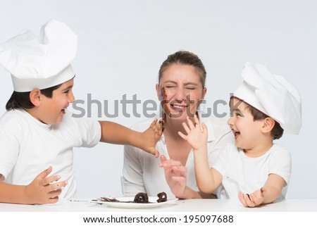 Family with mother and sons having joyful moments in kitchen with dirty hands and mouth, giving hard time to mother - stock photo