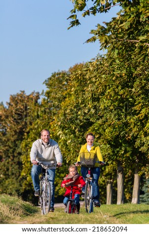Family with mother, father and daughter having family trip on bicycle or cycle in park - stock photo