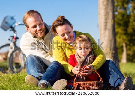 Family with mother, father and daughter having family trip on bicycle or cycle in park or country collecting chestnuts - stock photo