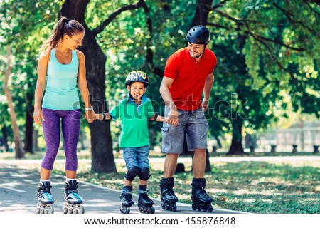 Family with one child roller skating in park - stock photo