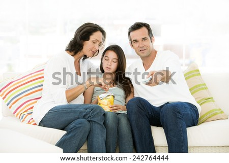 Family with one child watching tv - Father using remote control - Mother and daughter eating crisps - stock photo
