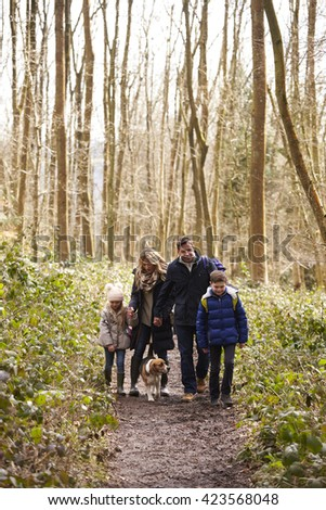 Family with pet dog walking in a wood, vertical - stock photo