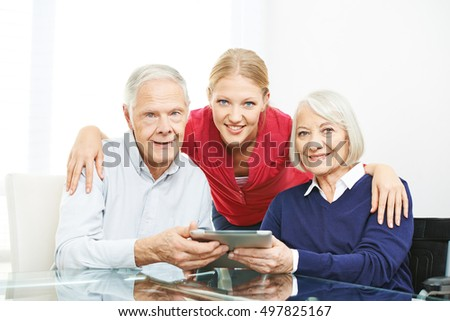Family with senior couple and tablet computer using the internet