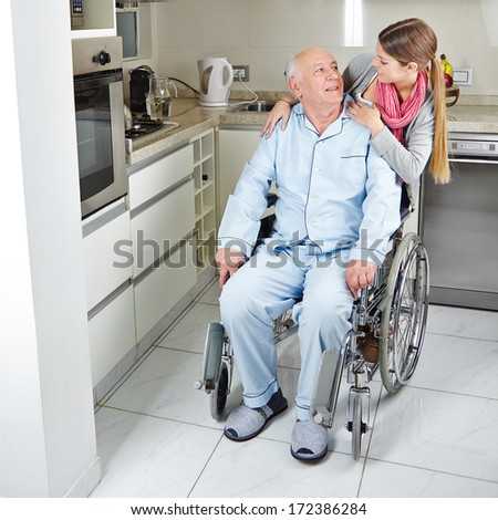 Family with senior man in wheelchair at home in the kitchen - stock photo