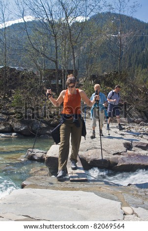 Family with senior parents and a young daughter hiking in the mountains - stock photo