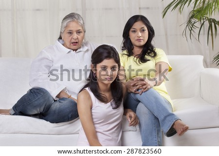 Family with serious expression watching television - stock photo