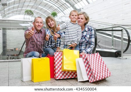 Family with shopping bags in the shopping center showing thumbs up