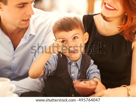 family with son having fun in a cafe eating desserts and fun