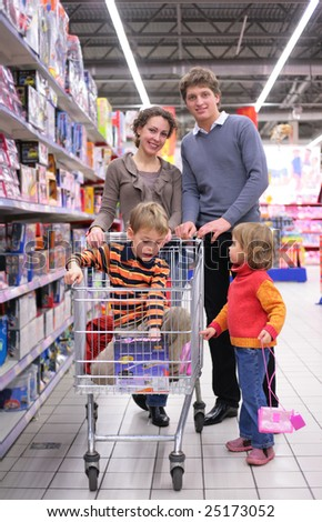 Family with son in cart and little girl in shop, focus on boy