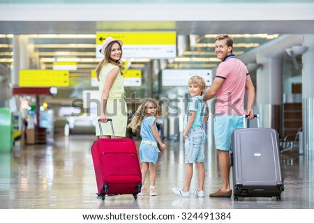 Family with suitcases in the airport - stock photo