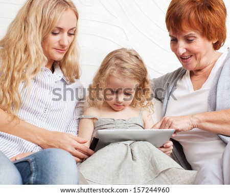 Family with tablet computer at sofa. Mother, grandmother and little girl at home on sofa. Generation - stock photo