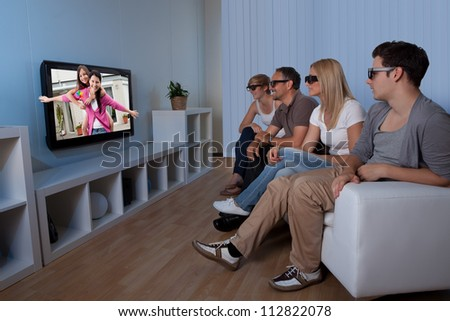 Family with teenage children sitting together on a couch eating bowls of popcorn wearing 3d glasses and watching the television