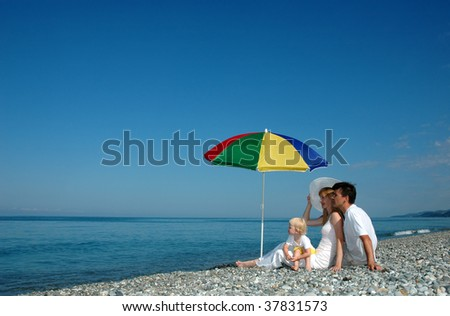 Family with the small child sit on a beach - stock photo
