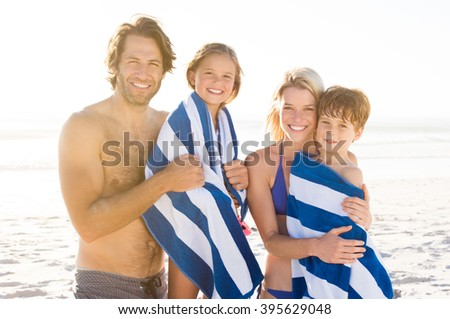 Family with their children draped in towel at beach after swim. Portrait of smiling parents with daughter and son after swimming. Family with two children looking at camera.