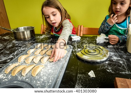 Family with twin girls is making home made pastry dumplings tortellini or ravioli. - stock photo