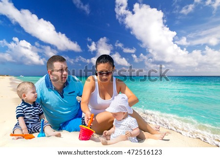 Family with twins on sun holidays at the tropical beach