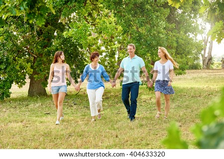 Family with two adult daughters walking happily together and holding hands in a green summer park with grass and leafy trees