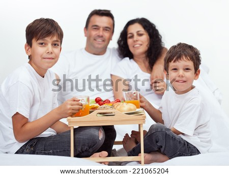 Family with two boys having breakfast in bed - with parents in background - stock photo