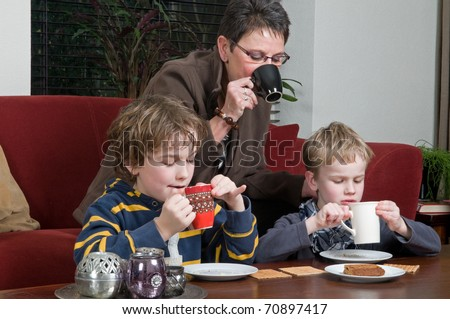 Family with two brothers and grandma in a livingroom - stock photo