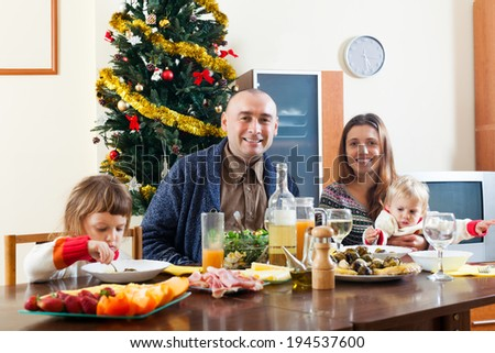 Family with two children  celebrating Christmas  over celebratory table at home  interior