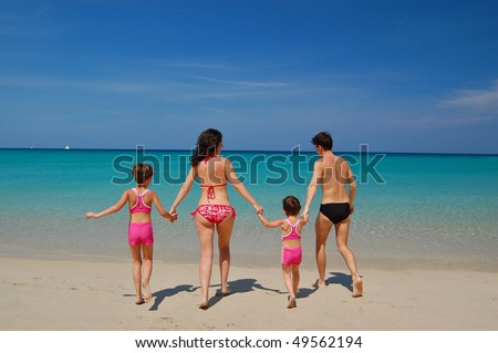 Family with two children in swimming suits on the tropical beach. Family vacation - stock photo