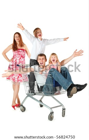 family with two children. joyful father with son and daughter is sitting in shopping basket. mother is standing behind shopping basket. isolated. - stock photo