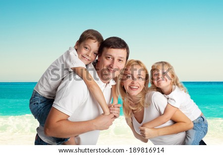 Family with two children on the beach - stock photo