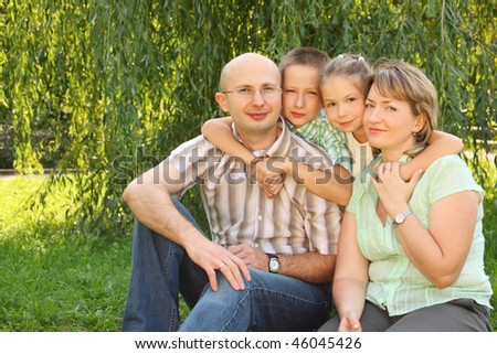 family with two children sitting at the grass near osier and looking at camera - stock photo