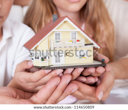 Family With Two Children Sitting On Couch Holding Miniature Model Of House At Home