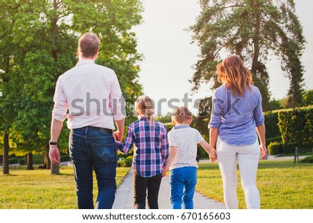 family with two children walking in green summer park, view from the back