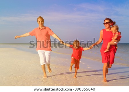 family with two kids having fun on tropical beach - stock photo